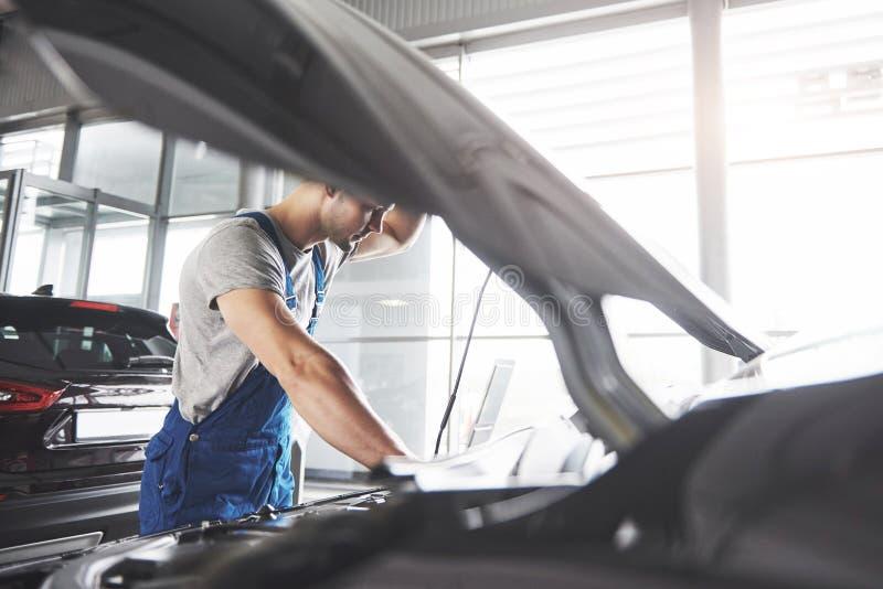 Décrivez montrer le travailleur musculaire de service de voiture réparant le véhicule photographie stock libre de droits
