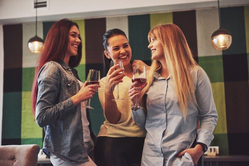 Décrivez présenter le groupe heureux d'amis avec le vin rouge photo stock