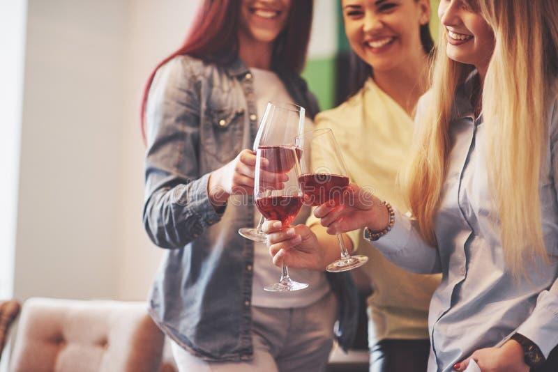 Décrivez présenter le groupe heureux d'amis avec le vin rouge photos stock