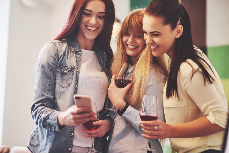 Décrivez présenter le groupe heureux d'amis avec le vin rouge photographie stock