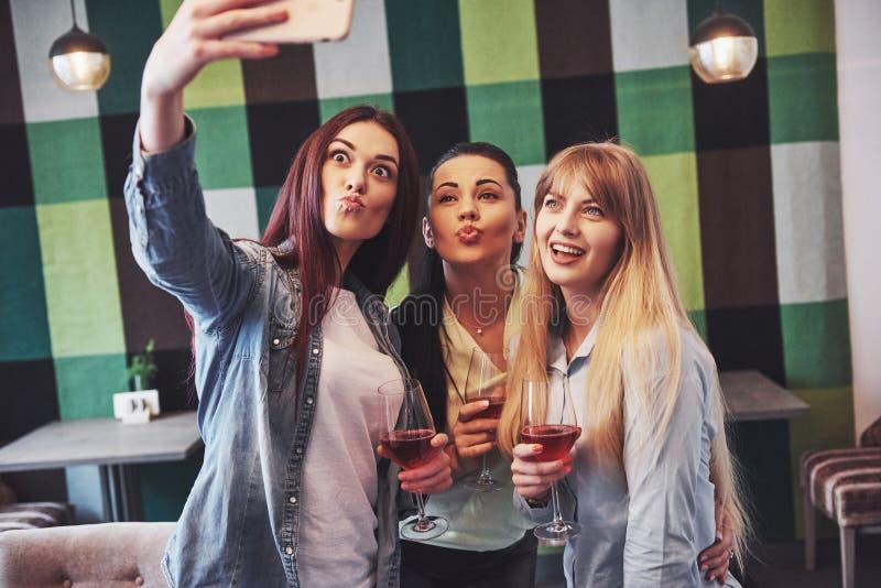 Décrivez présenter le groupe heureux d'amis avec le vin rouge prenant le selfie photographie stock