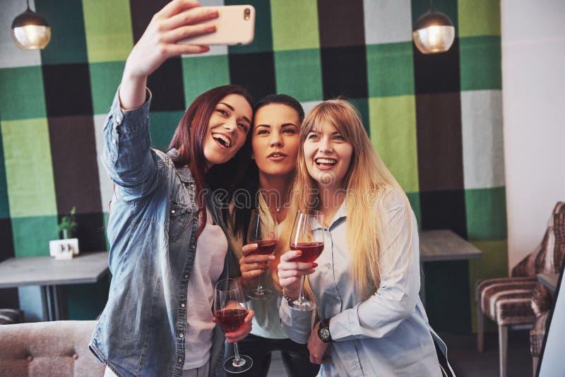 Décrivez présenter le groupe heureux d'amis avec le vin rouge prenant le selfie photo stock