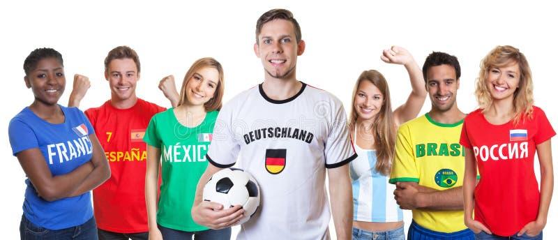 Défenseur allemand du football avec la boule et fans d'autres pays photos libres de droits