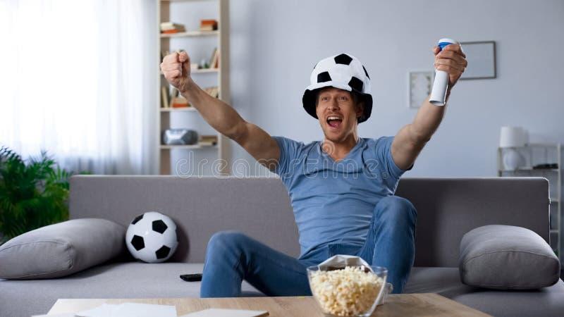 Défenseur ardent du football dans la réjouissance de chapeau de fan à la penalty marquée, victoire photographie stock libre de droits