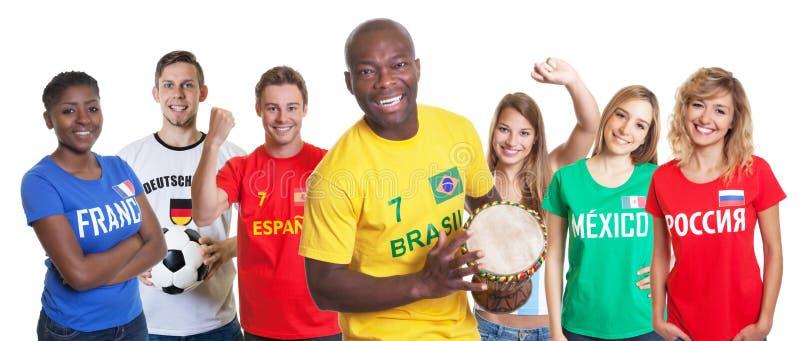 Défenseur brésilien du football avec le tambour et les fans de l'autre countri image libre de droits