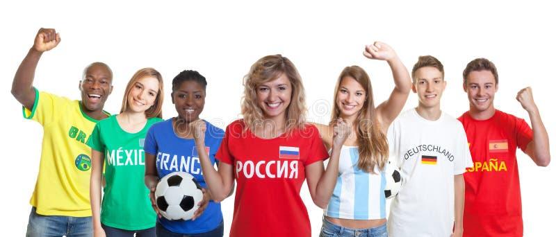 Défenseur russe encourageant du football avec des fans d'autres pays image libre de droits