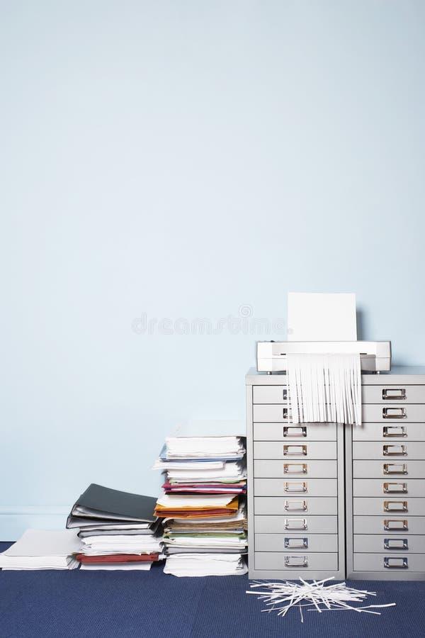 Défibreur sur la pile de classeur d'écritures sur le plancher dans le bureau images libres de droits