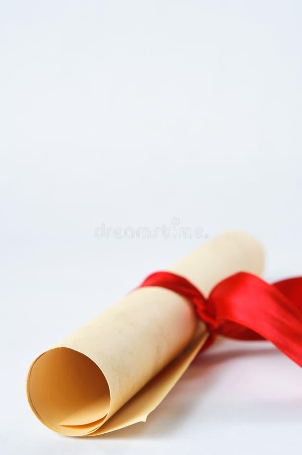 Défilement de diplôme avec la bande rouge photographie stock