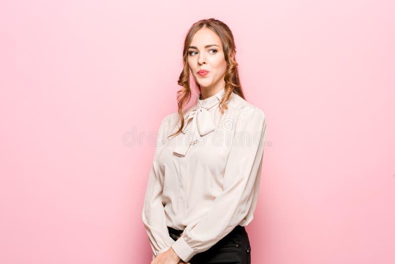 Déjeme pensar Mujer pensativa dudosa con la expresión pensativa que toma la decisión contra fondo rosado fotografía de archivo libre de regalías