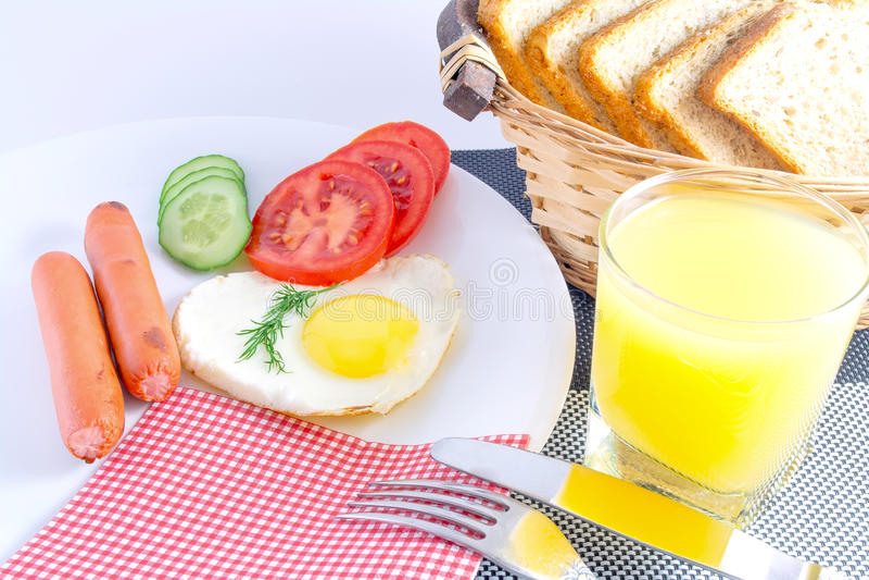 Déjeunent sur un oeuf au plat de table dans les saucisses frites en forme de coeur, légumes découpés en tranches frais, jus, bre  photographie stock libre de droits