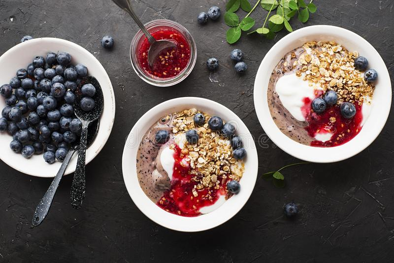 Déjeunent une cuvette avec les smoothies de myrtille, le yaourt pur, la granola cuite au four faite maison et la confiture crue f photos stock