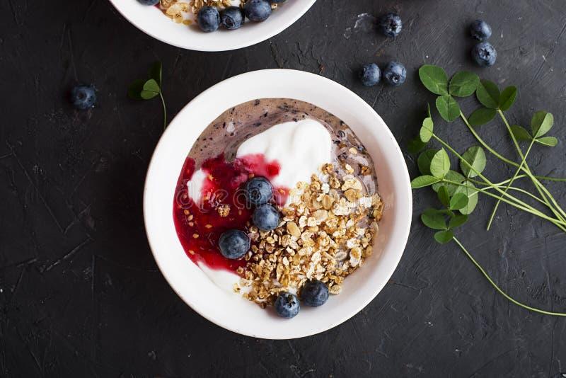 Déjeunent une cuvette avec les smoothies de myrtille, le yaourt pur, la granola cuite au four faite maison et la confiture crue f photo libre de droits