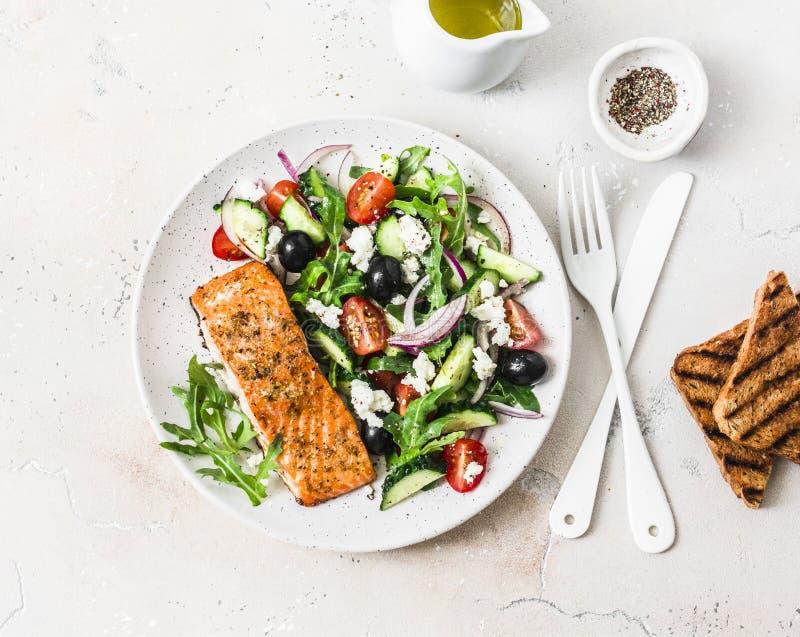 Déjeuner équilibré sain - a grillé les saumons de filet de poissons et les tomates rouges, concombres, les olives, salade grecque photos libres de droits