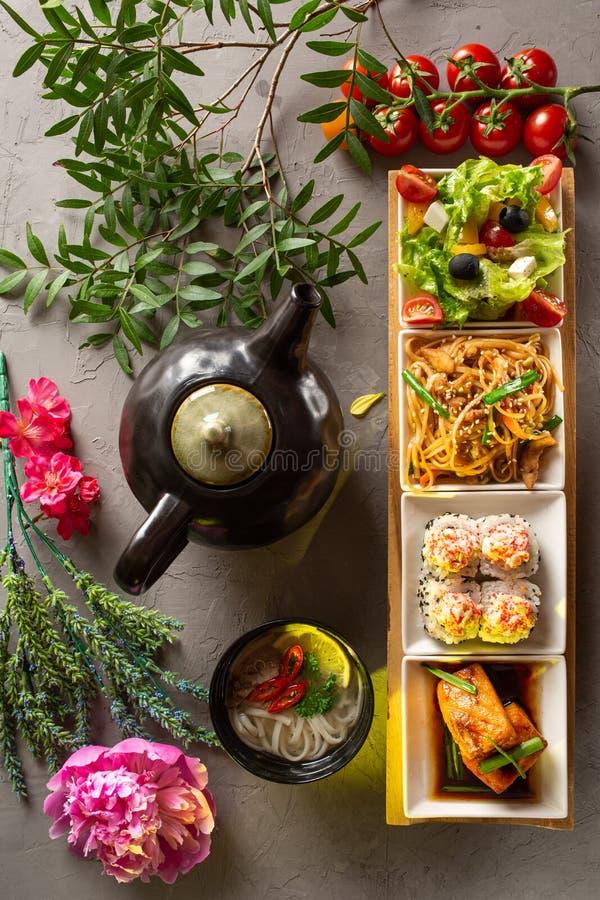 Déjeuner complet Salade grecque, nouilles de verre, petits pains, filet de saumon, soupe aux nouilles et théière avec thé sur fon photo stock