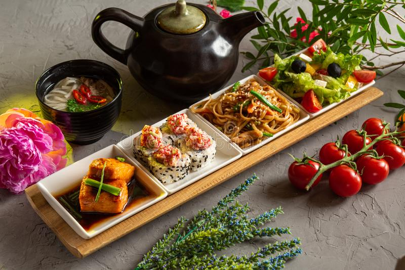 Déjeuner complet Salade grecque, nouilles de verre, petits pains, filet de saumon, soupe aux nouilles et théière avec thé sur fon photo libre de droits