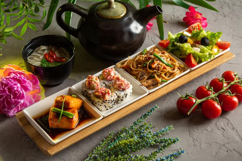 Déjeuner complet Salade grecque, nouilles de verre, petits pains, filet de saumon, soupe aux nouilles et théière avec thé sur fon images libres de droits