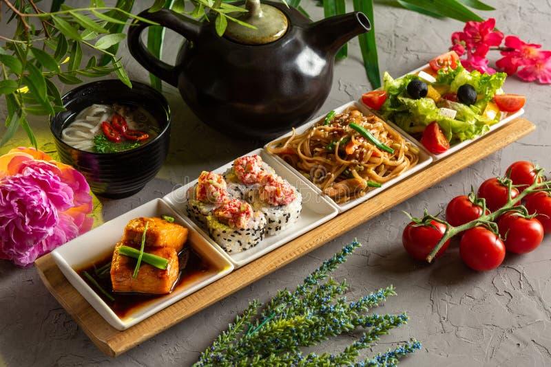 Déjeuner complet Salade grecque, nouilles de verre, petits pains, filet de saumon, soupe aux nouilles et théière avec thé sur fon image libre de droits