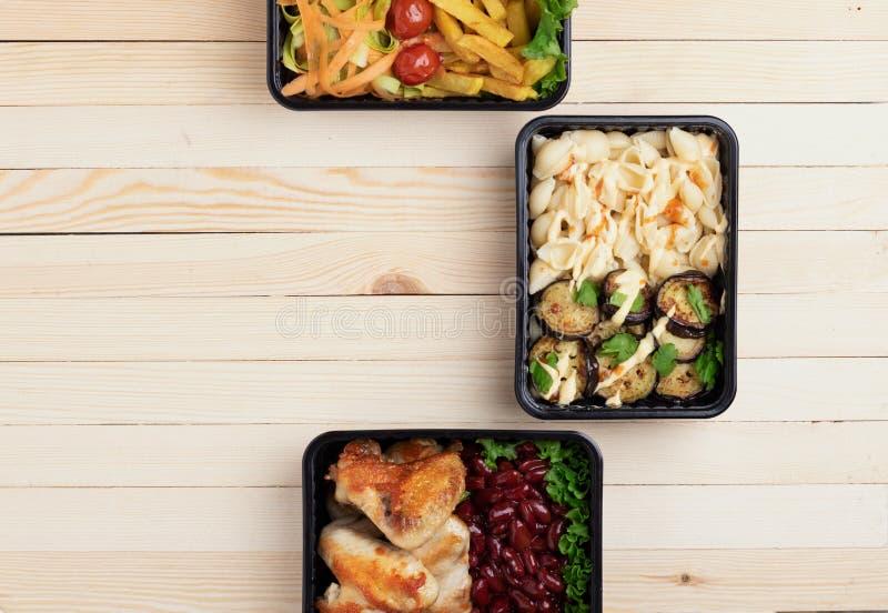 Déjeuner d'affaires dans des boîtes à nourriture, ailes de poulet rôti, légumes cuits à la vapeur, viande cuite, repas prêt à man images libres de droits