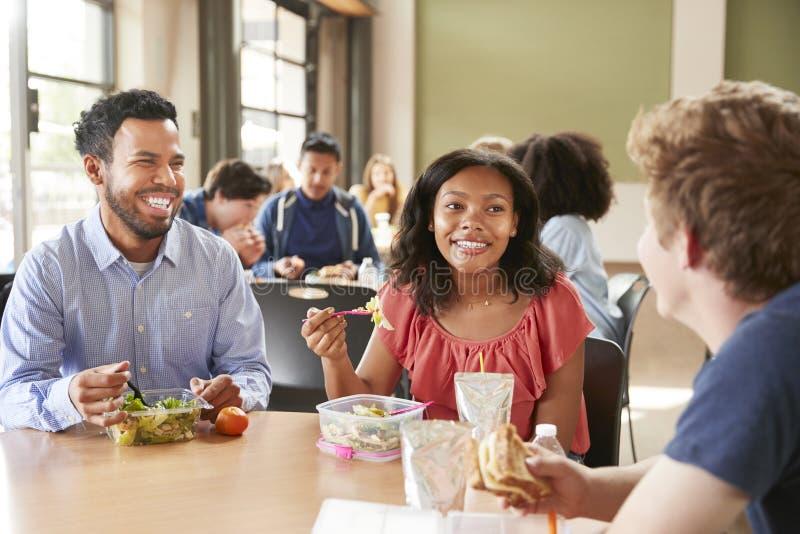 Déjeuner d'And Students Eating de professeur dans la haute cafétéria de l'école pendant le renfoncement photographie stock libre de droits