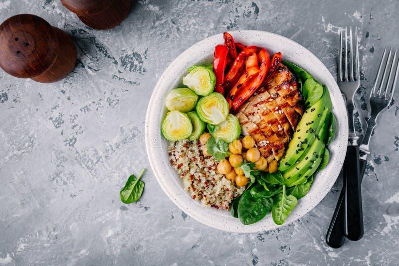 Déjeuner végétal de cuvette avec le poulet et le quinoa grillé, les épinards, l'avocat, les choux de bruxelles, le paprika et le  photographie stock libre de droits