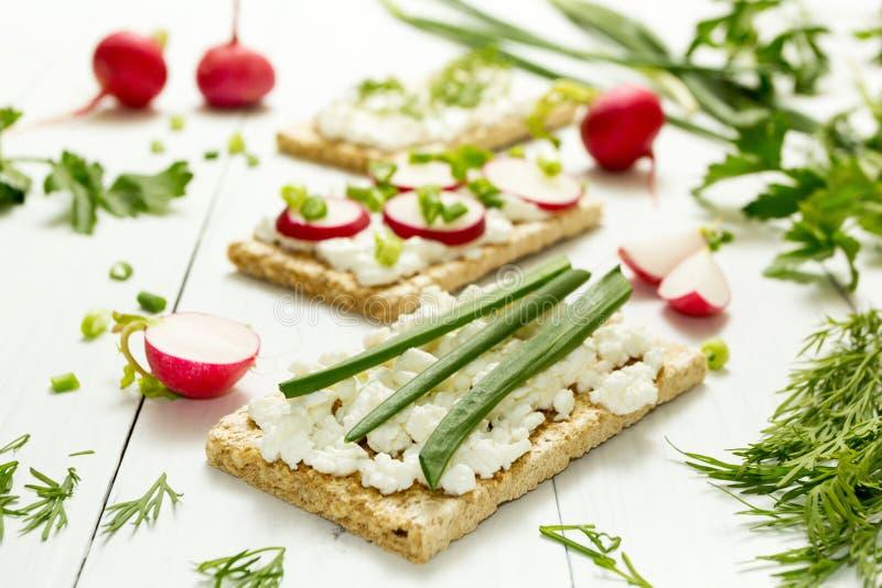 Déjeuner végétarien léger avec le fromage blanc, les herbes et le radis sur un fond blanc Foyer sélectif photo stock