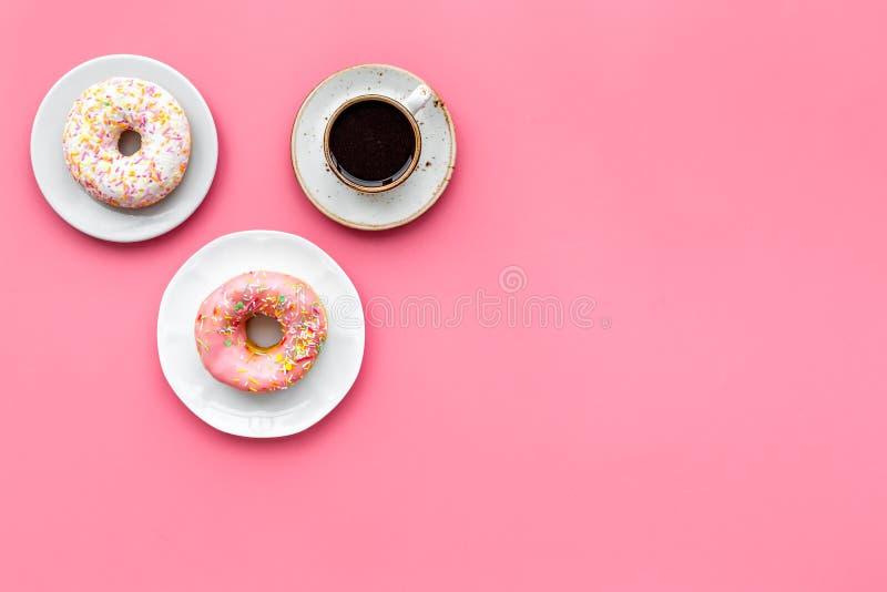 Déjeunez avec du café, des butées toriques et des fleurs sur la maquette rose de vue supérieure de fond photos stock
