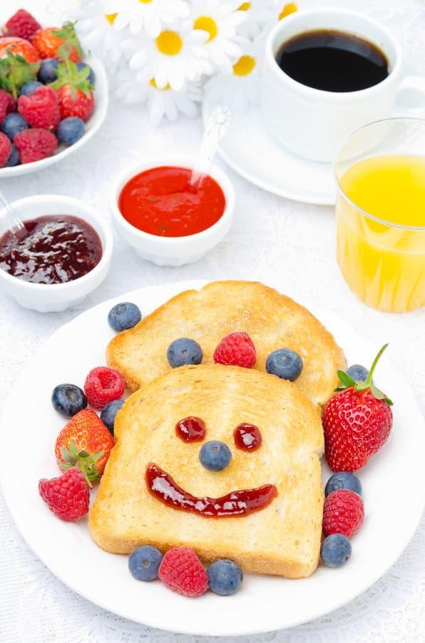 Déjeunez avec du pain grillé de sourire, baies fraîches, confitures, jus, café photographie stock