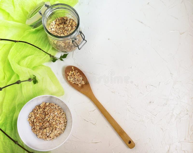 Déjeunez avec la farine d'avoine dans les plats blancs sur une table en bois, avec un coureur vert clair et des branches d'arbre  images stock