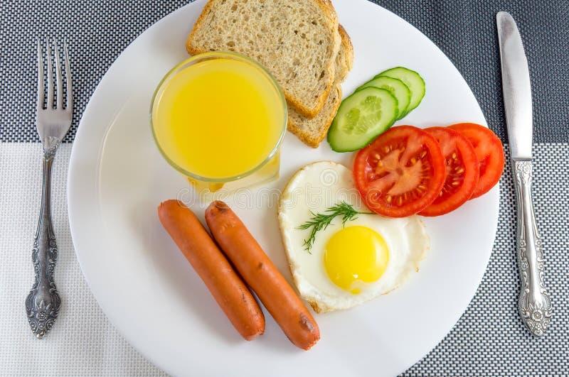 Déjeunez d'un plat blanc sur un oeuf au plat noir et blanc de table dans une saucisse en forme de coeur et frite, légumes frais photos libres de droits