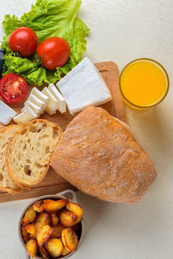 Déjeunez du pain, fromage, tomates, pommes de terre, partout dans la salade et un verre de jus d'orange image stock