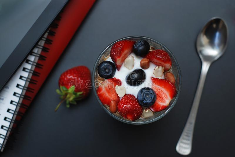 Déjeunez pour la santé, les fraises fraîches, Blueberies, avec la table de bureau de noir de farine d'avoine Tablette, ordinateur photos libres de droits