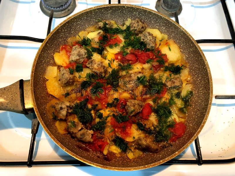 Déjeunez sur une main rapide du célibataire Viande, pommes de terre, tomate, herbes, oignons et d'autres vitamines dans une poêle photos stock