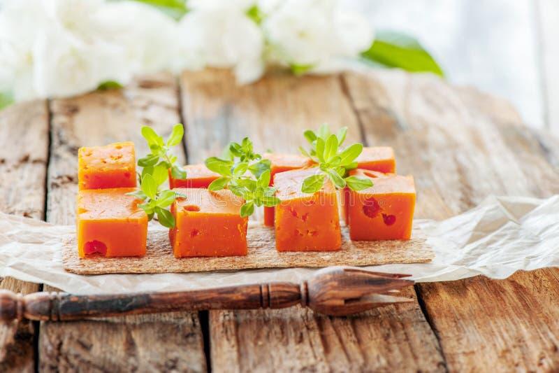 Délicatesses, fromages épicés Le cheddar rouge, sur un beau fond en bois texturisé avec des brindilles de savoureux est un casse- image libre de droits