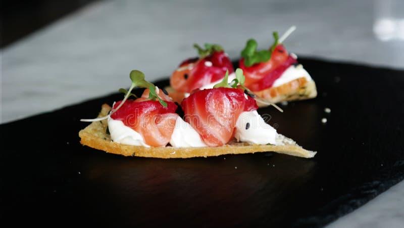 Délicieux amusez l'apéritif de bouche, les saumons traités avec des betteraves, les échecs et la fleur orange photo libre de droits