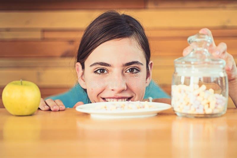 Délicieux ou néfaste Vitamine ou sucre Joli regard de femme à la pomme et aux guimauves Organique et naturel ou doux et image libre de droits