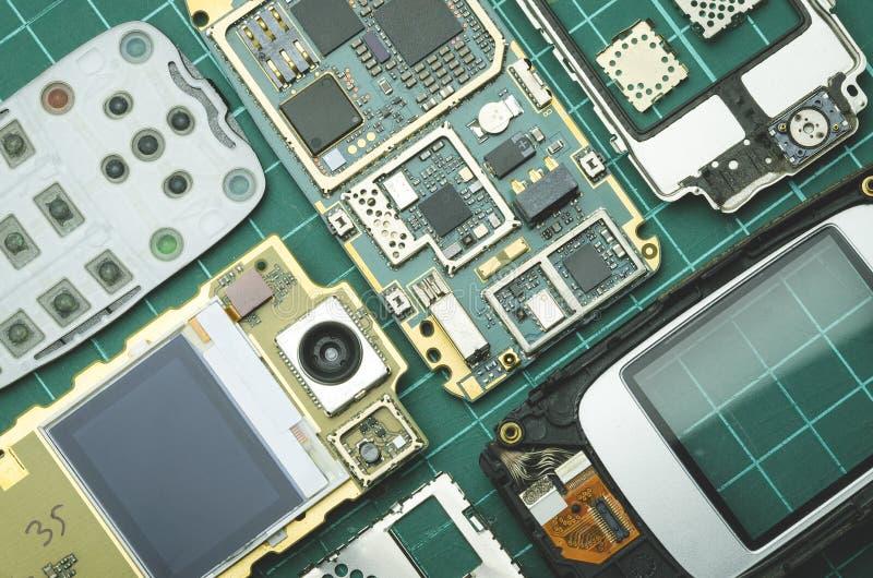 Démantelé pour le vieux téléphone portable de pièces de rechange sur le plan rapproché vert de fond photos stock