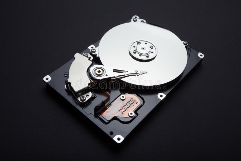 Démontez le disque dur de serveur, la surface magnétique et les têtes de lecture sur un fond noir images stock