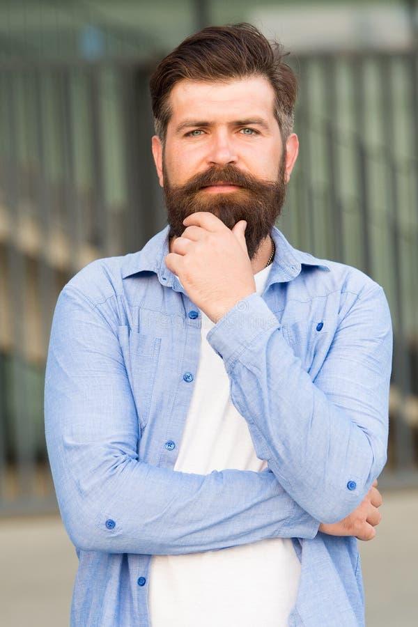 Dénommer des astuces de cheveux Créez le style personnel avec la pilosité faciale Hippie avec le fond urbain élégant de barbe et  photographie stock libre de droits