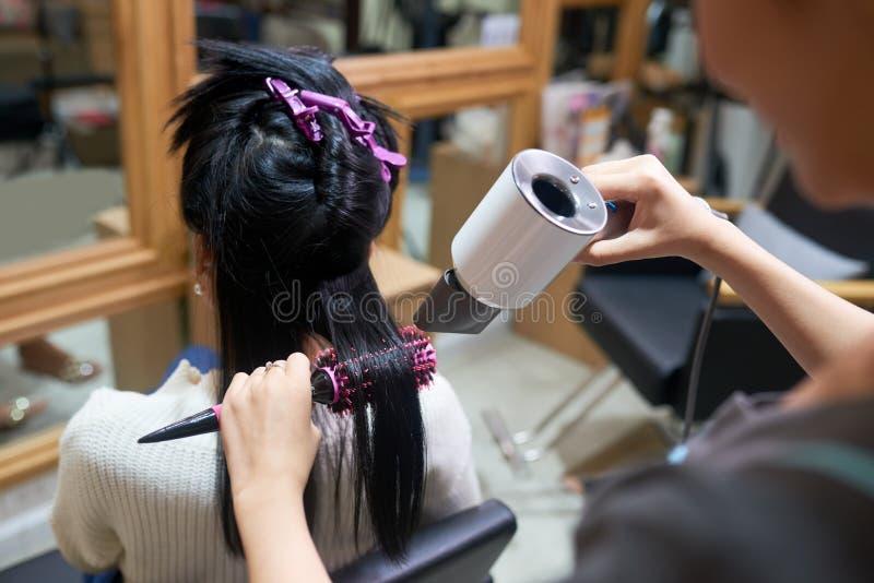 Dénommer des cheveux utilisant le sèche-cheveux images stock