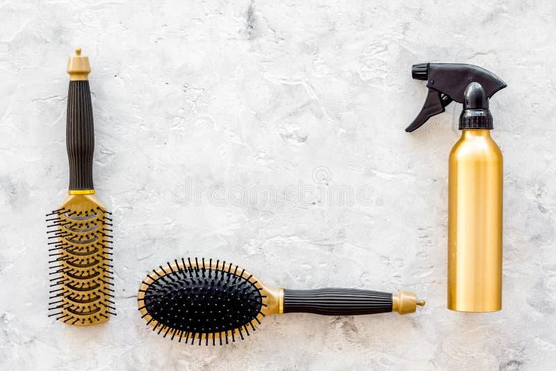Dénommer des instruments de cheveux avec des peignes et des brosses dans le raseur-coiffeur sur la maquette en pierre de vue supé photographie stock