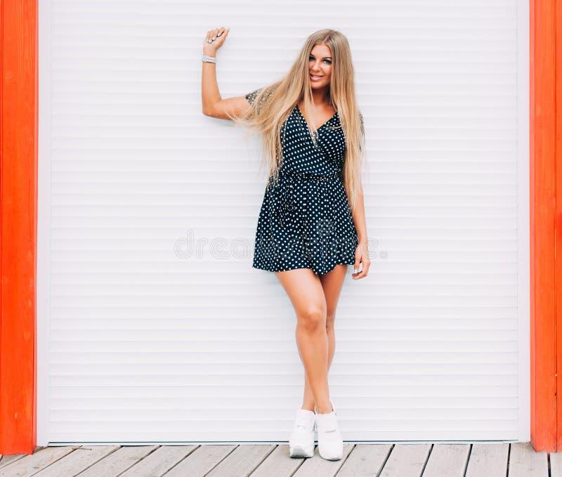 Dénommez le portrait de la pose extérieure de femme blonde sexy en été Façonnez le butin habillé dans la robe et des espadrilles  photographie stock libre de droits