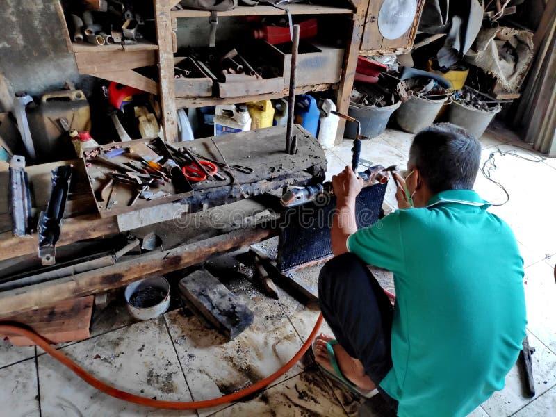 Dépanneur de radiateur en nettoyant et en réparant les radiateurs cassés dans de vieilles voitures images libres de droits