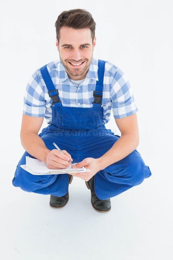 Dépanneur heureux se tapissant tout en écrivant sur le presse-papiers photographie stock