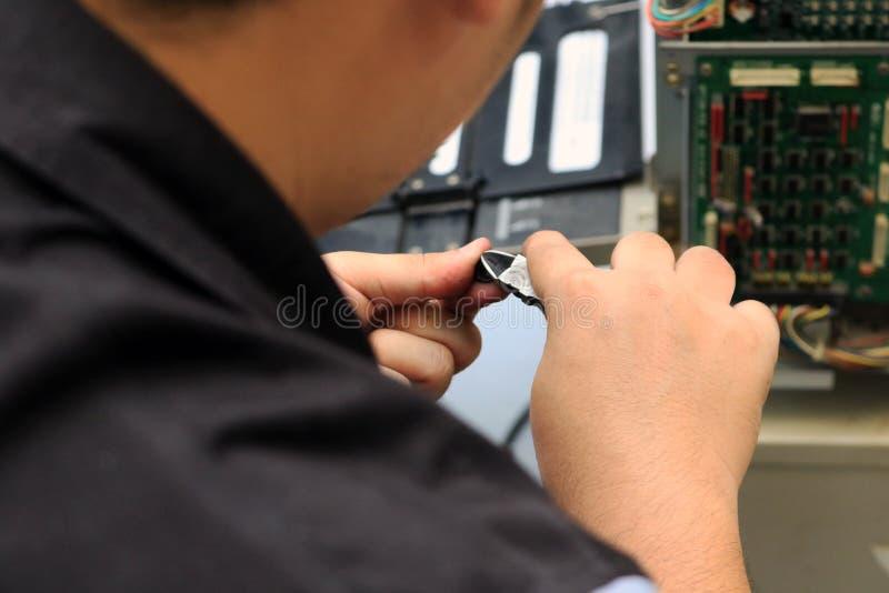 Dépanneur tenant des pinces pour des difficultés ou l'entretien et le matériel électronique de soutien images stock