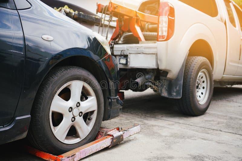 Dépanneuse prenant et remorquant la vieille voiture décomposée sur un bord de la route photos stock