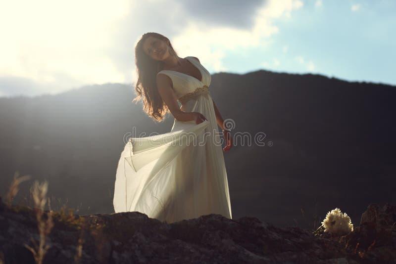 Dépassement léger de coucher du soleil par la robe de jeune mariée image stock