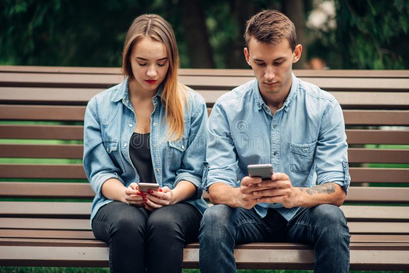 Dépendance de téléphone, couple d'intoxiqué utilisant des smartphones images stock