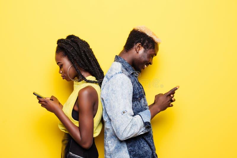 Dépendance de téléphone Portrait d'un jeune couple afro-américain se tenant de nouveau au dos utilisant des téléphones portables  photo stock