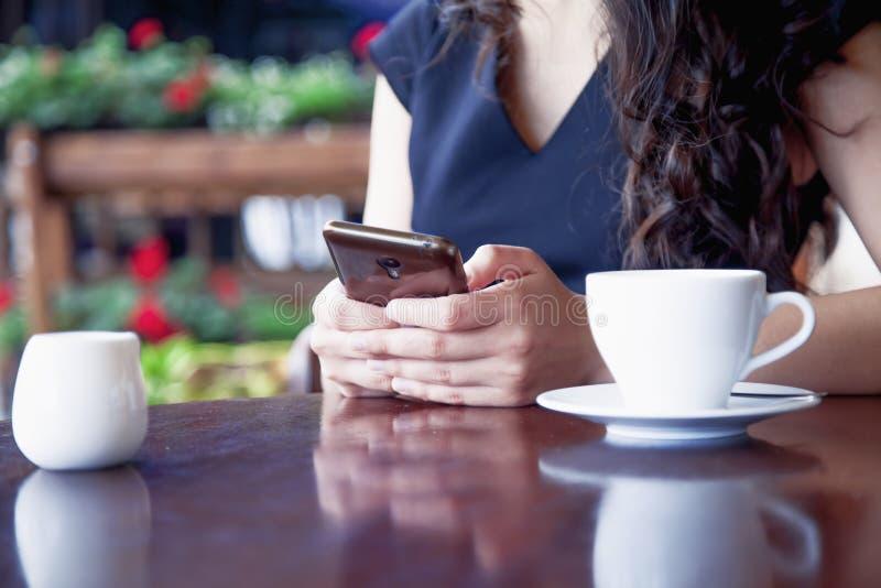 Dépendance sociale de media jeune belle femme tenant un smartpho photo stock