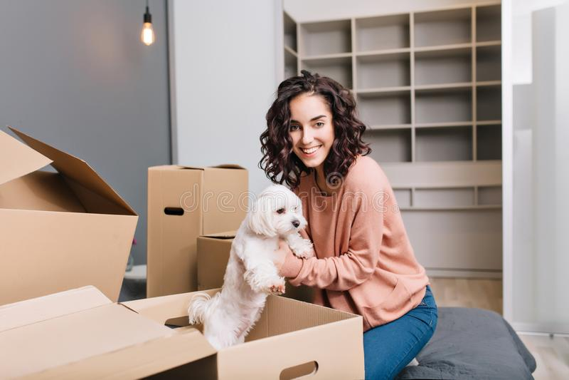 Déplacement au nouvel appartement moderne de la jeune femme joyeuse trouvant un petit chien blanc dans la boîte de carton Sourire photographie stock